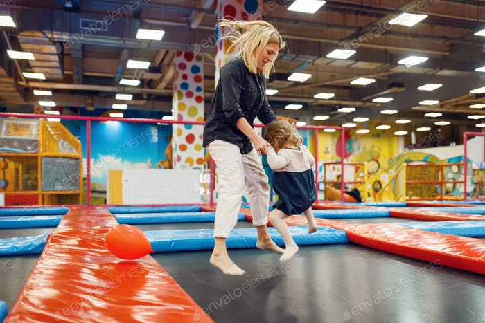 Mother and little girl jumping on a trampoline