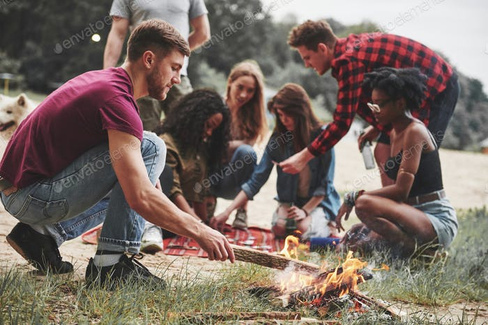 Classic campfire party. Group of people have picnic on the beach. Friends have fun at weekend time