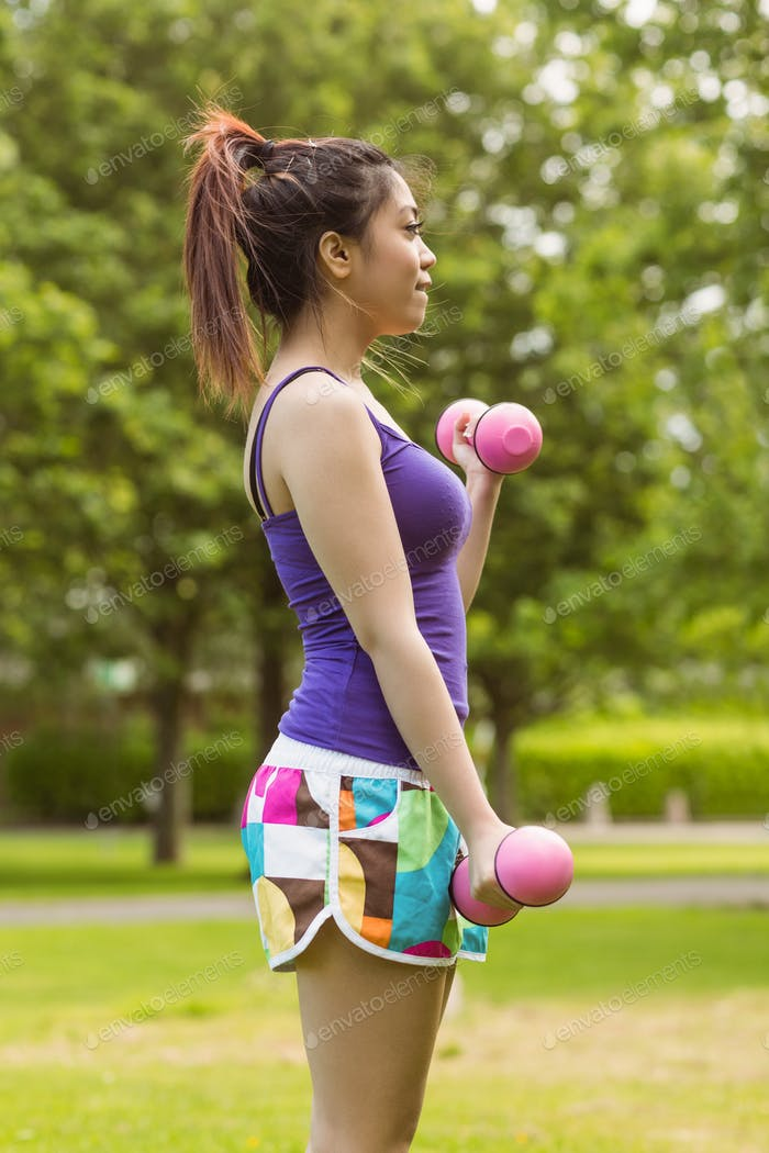 Side view of healthy and beautiful young woman lifting dumbbells in park