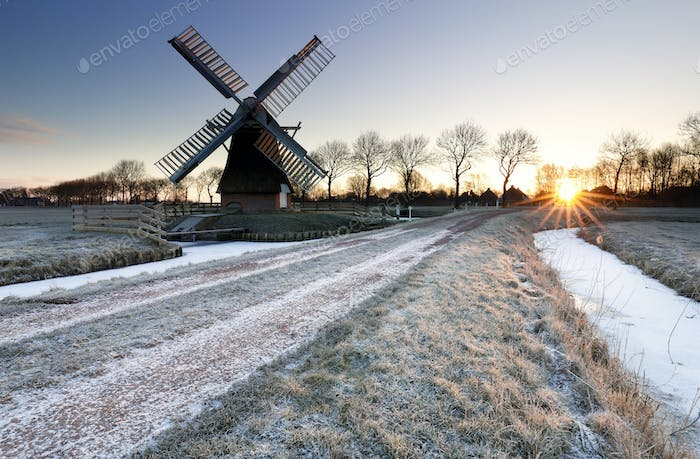 wintry sunrise over frozen countryside with windmill