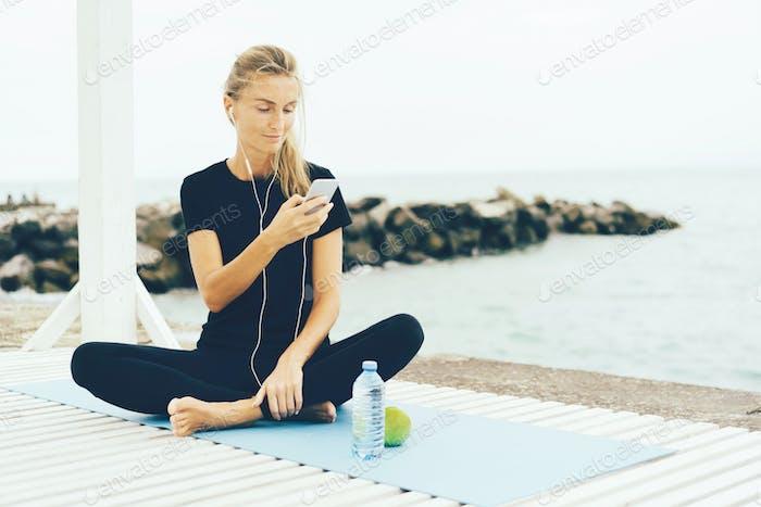 Junge sportliche Frau hören Musik auf dem Smartphone nach dem Training draußen an der Küste.