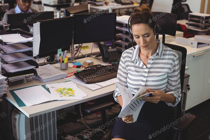 Businesswoman holding documents by desk at office