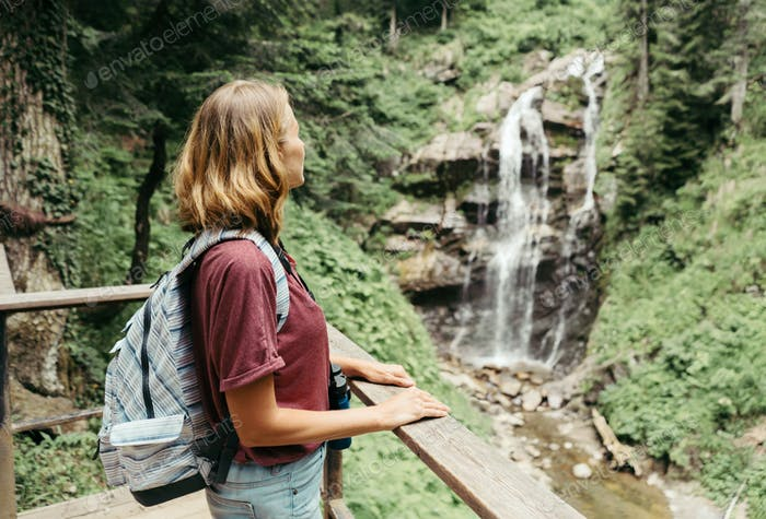 A woman travels around the countryside neighborhood in the rainforest and looks at the waterfall.