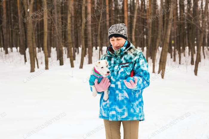 Pets owner and winter concept - Middle aged woman playing with her jack russell terrier dog in snowy