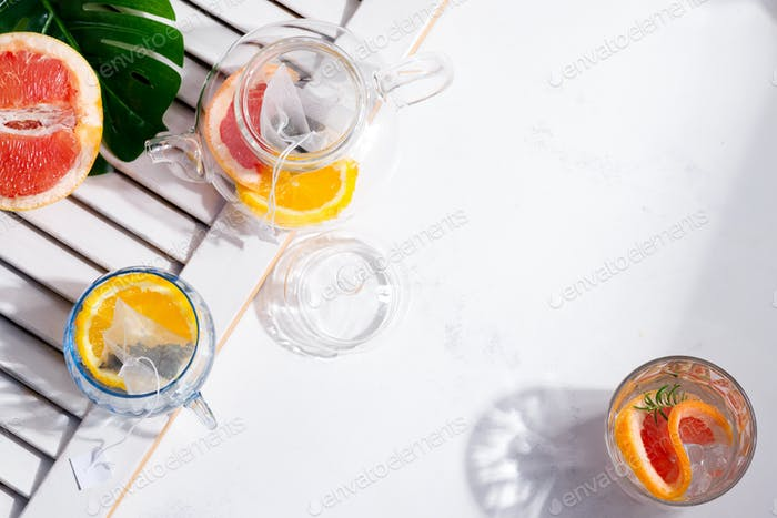 Refreshing summer homemade cold tea drinks in the glass on a white background with part of wooden
