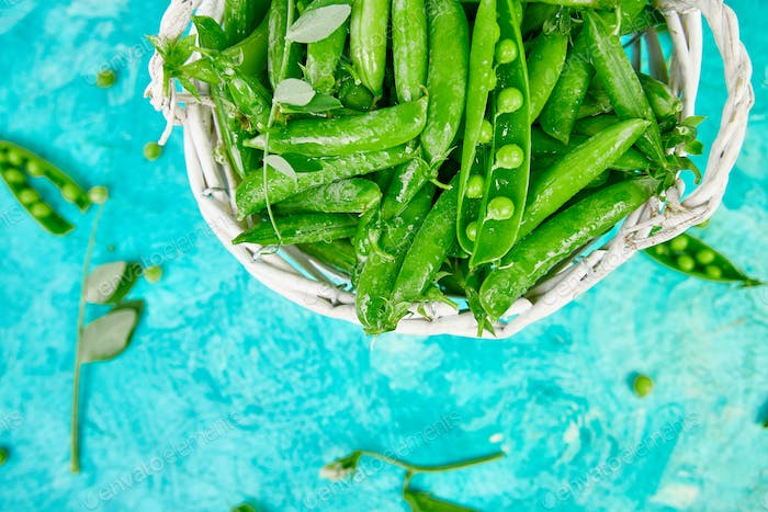 fresh green peas on blue background.