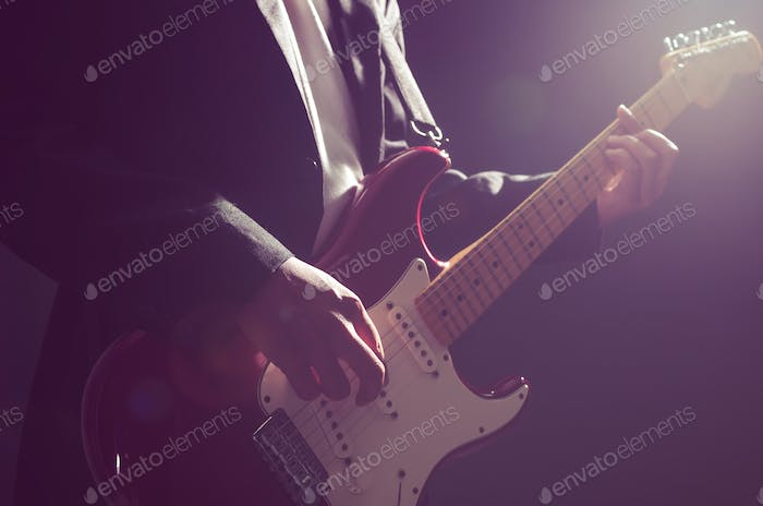 Closeup musician playing the guitar on dark background with lens flare from spot light