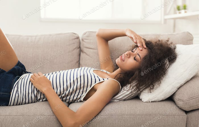 Sad black girl feeling pain lying on sofa