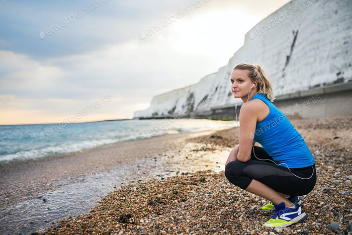 Young sporty woman runner with earphones resting on the beach outside.