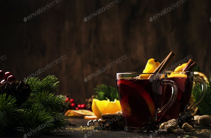 Xmas hot mulled wine with spices and fruits on wooden rustic table. Traditional Christmas hot drink