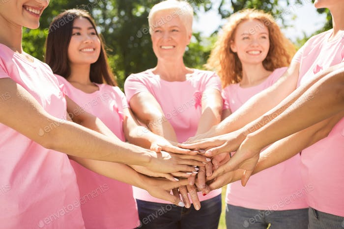 Diverse Women Wearing Breast Cancer Ribbon T-Shirts Holding Hands
