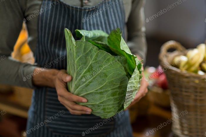 Vendor holding cabbage at the grocery store