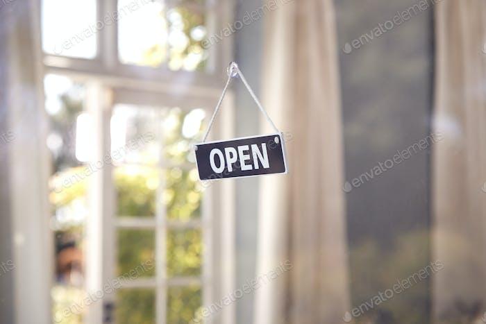 Schild öffnen, das während der Gesundheitspandemie im Schaufenster hängt