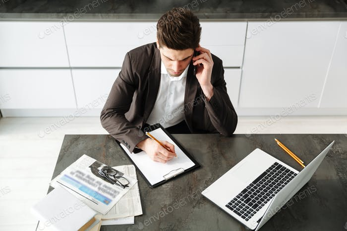 Concentrated young businessman working talking by mobile phone.
