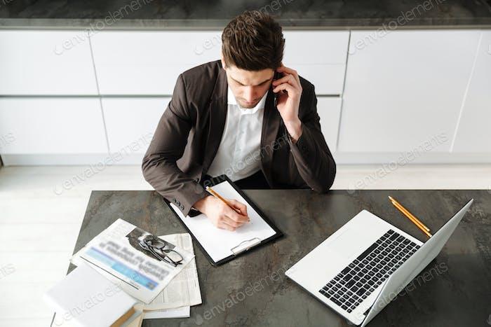 Konzentrierter junger Geschäftsmann, der im Gespräch mit dem Handy arbeitet.