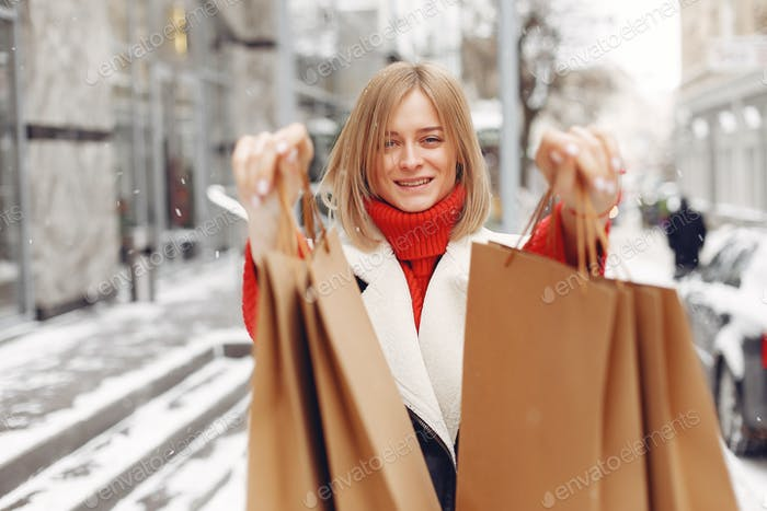 Woman carrying shopping bags at an outdoor shopping mall
