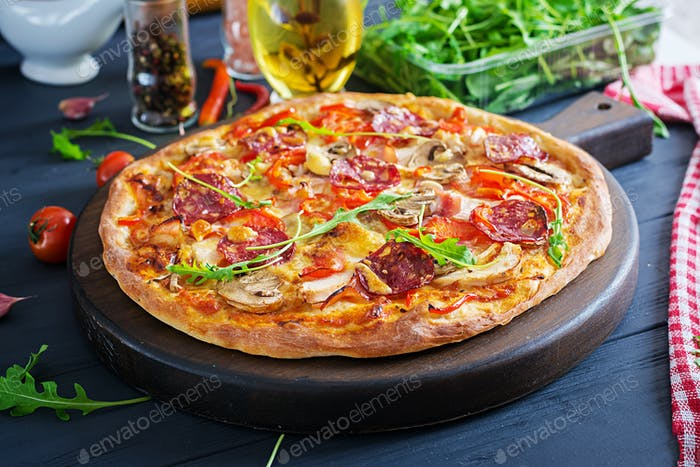 Fresh Italian pizza with chicken fillet, mushrooms, ham, salami, tomatoes, cheese