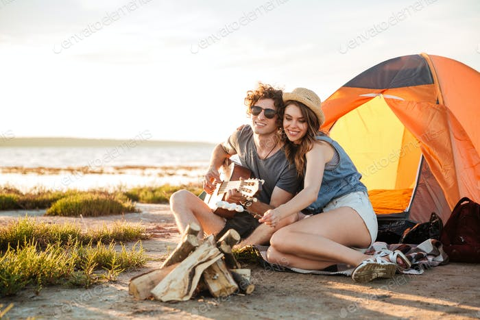 Paar spielen Gitarre und Braten Marshmallows auf Lagerfeuer zusammen
