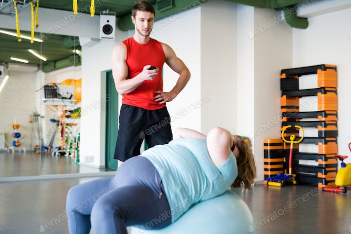 Obese Woman training in Fitness Club