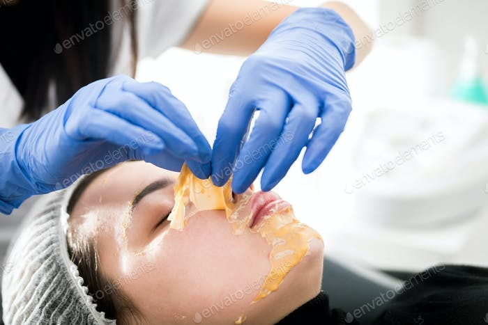 Beautician removing facial mask at cosmetic clinic, cosmetology treatment skincare face