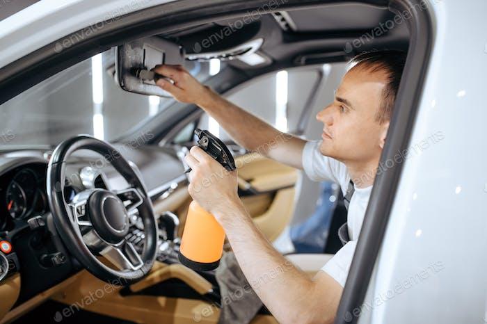 Arbeiter mit Spray befeuchtet Auto-Innenraum