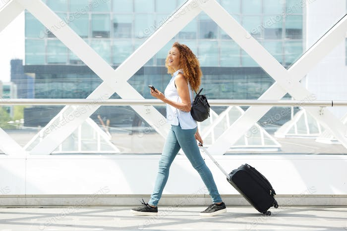 happy young woman walking with suitcase and mobile phone on station platform
