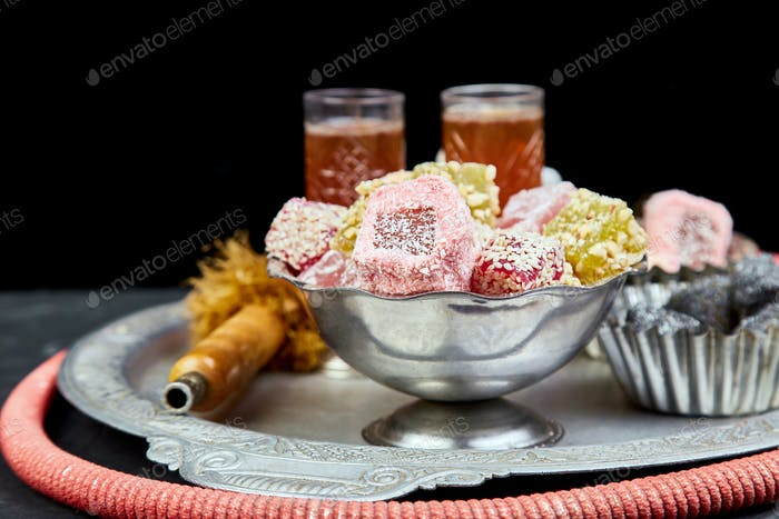 Set of various Turkish delight in bowl on metal tray near hookah tube