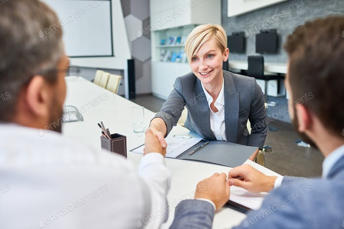 Successful Businesswoman Greeting Partners in Board Room