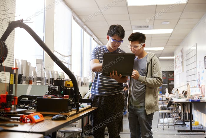 Two Male College Students Using Laptop Computer In Science Robotics Or Engineering Class