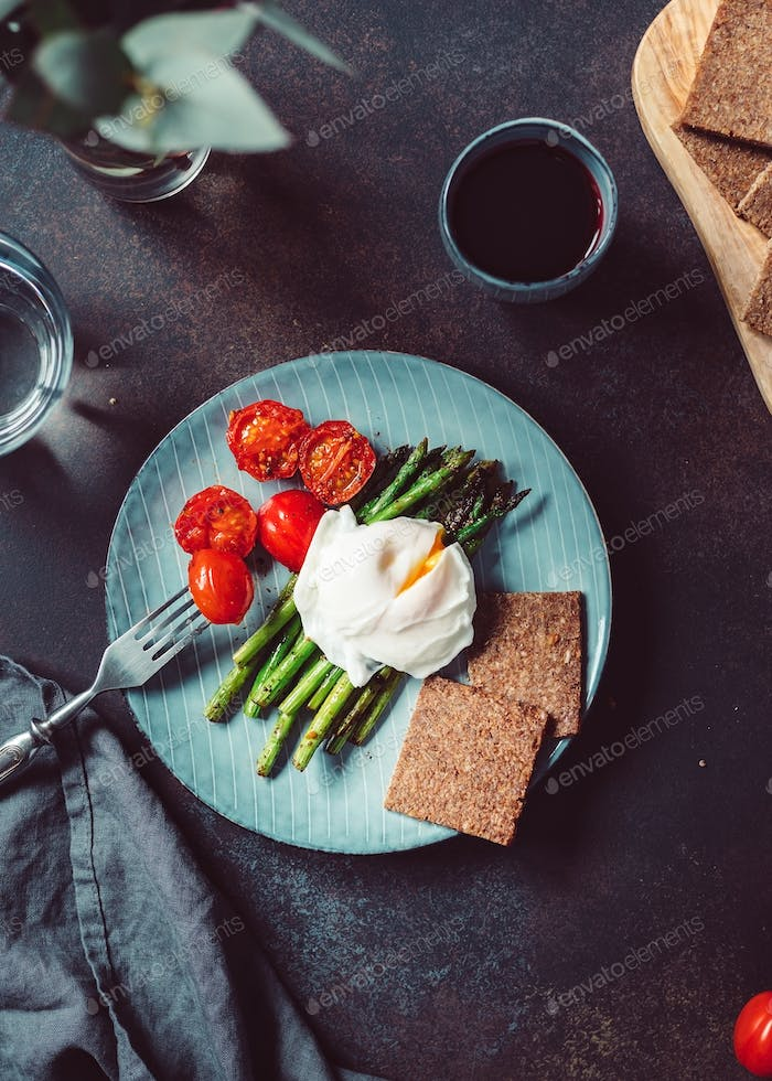 View from above on dinner or lunch for one, poached egg on grill asparagus and cherry tomatoes.