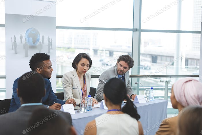 Front view of mixed race business people sitting at table in seminar