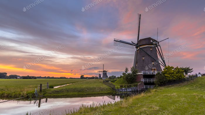 Three windmills in a row under beautiful sunset