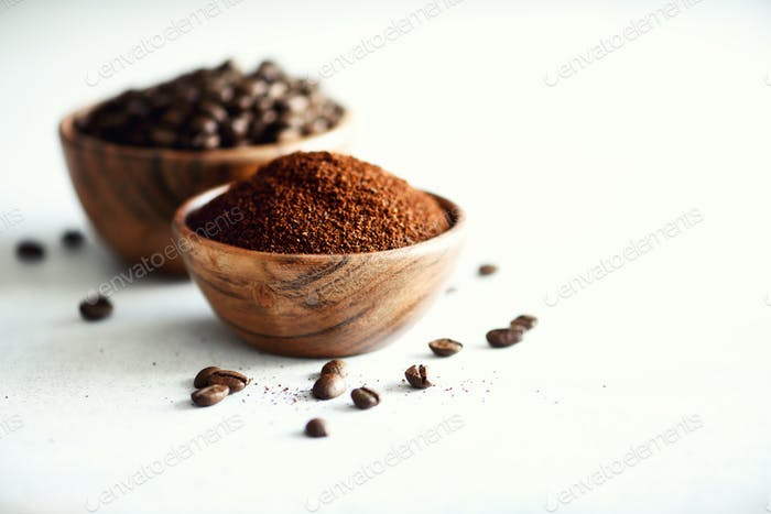 Ingredients for making caffeine drink - coffee beans, ground and instant coffee on light concrete