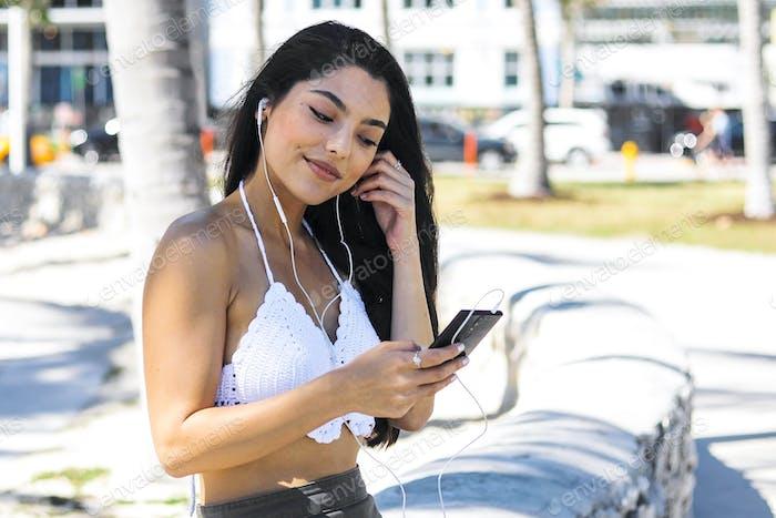 Confident trendy brunette listening to music outside
