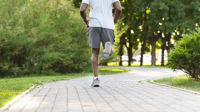 Athletic body of black runner, park background