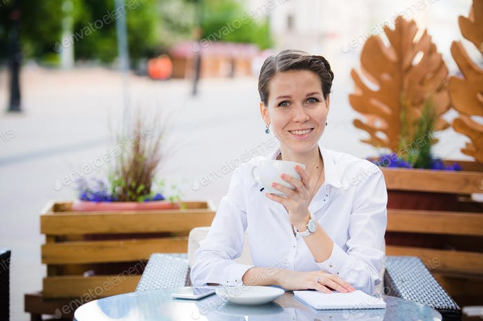 Lovely business woman with smile is sitting with touch pad in comfortable restaurant during