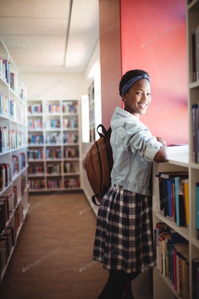 Portrait of schoolgirl reading book in library