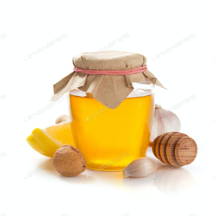 glass jar of honey on white background