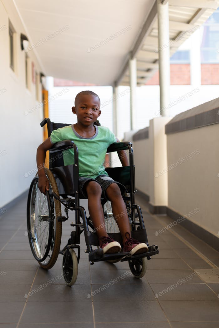 Disabled schoolboy looking at camerA in corridor at elementary school
