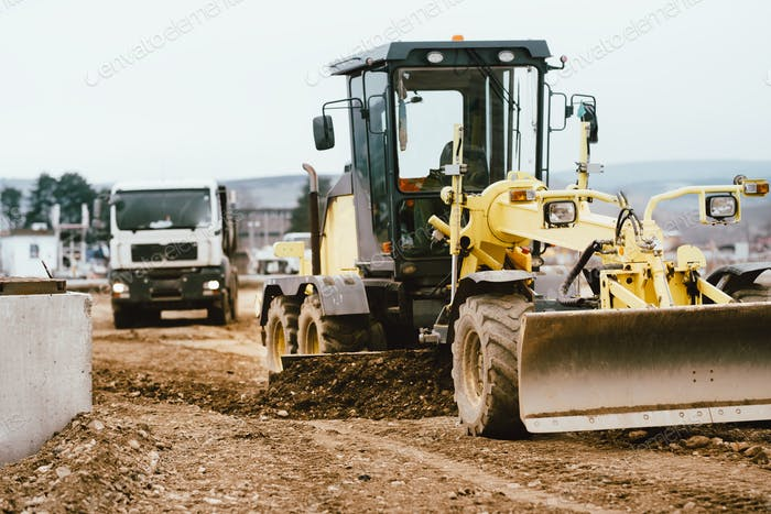 Industrial motor grader working at highway construction site