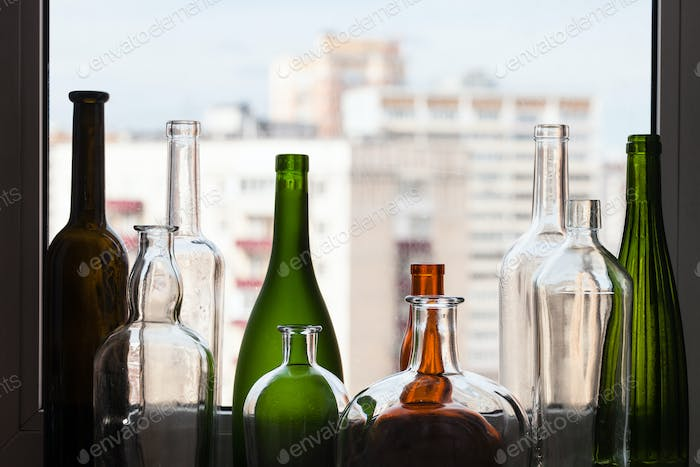various empty bottles on sill and view of city