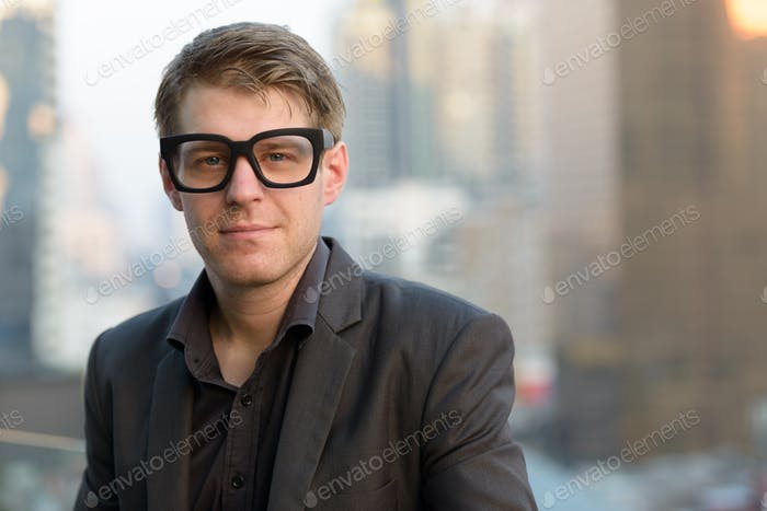 Face of young handsome nerd businessman with eyeglasses against view of the city