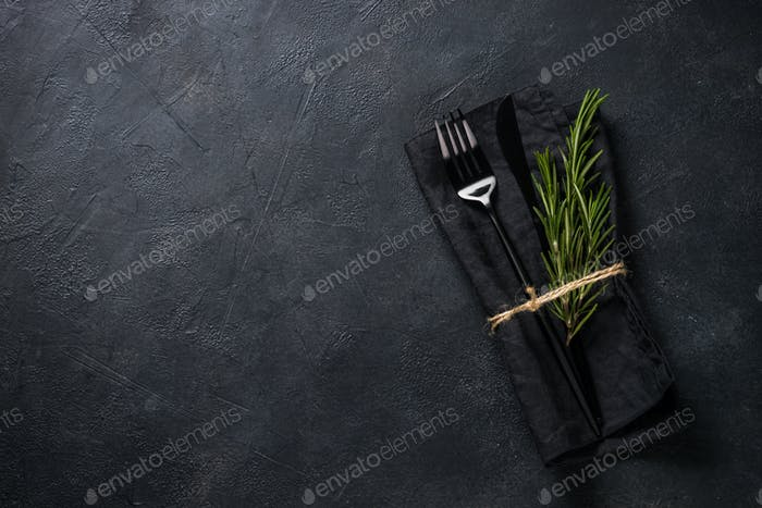 Black cutlery and napkin with a sprig of rosemary on black stone table top view
