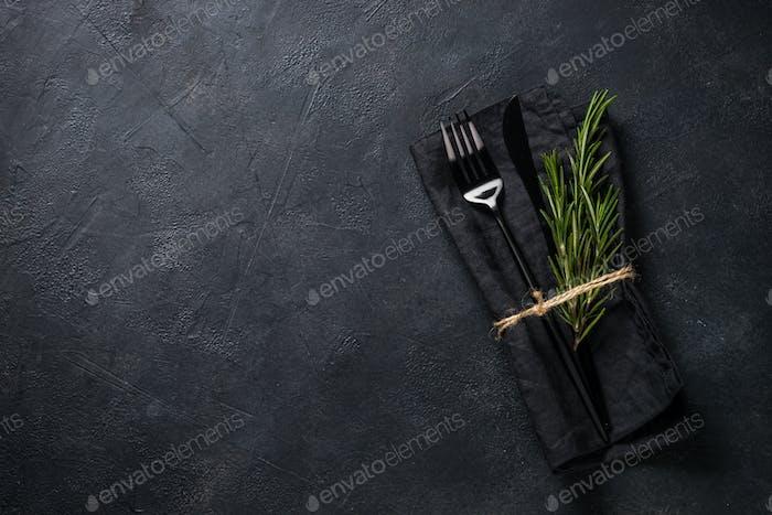 Schwarzes Besteck und Serviette mit einem Zweig Rosmarin auf schwarzem Stein Tischansicht
