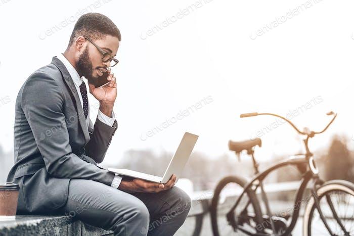 Rush job. Businessman sitting outdoors and using laptop