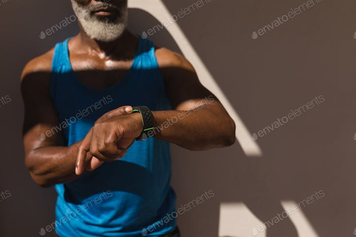 Mid section of senior African American man using smartwatch in the backyard of home