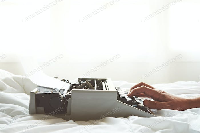 Men hands typing on vintage typewriter on  the bed