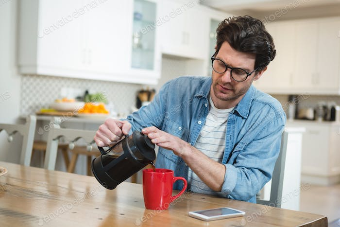 Man pouring coffee from french press into mug at home