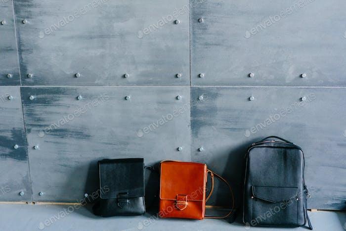 три кожаные сумки на сером фоне