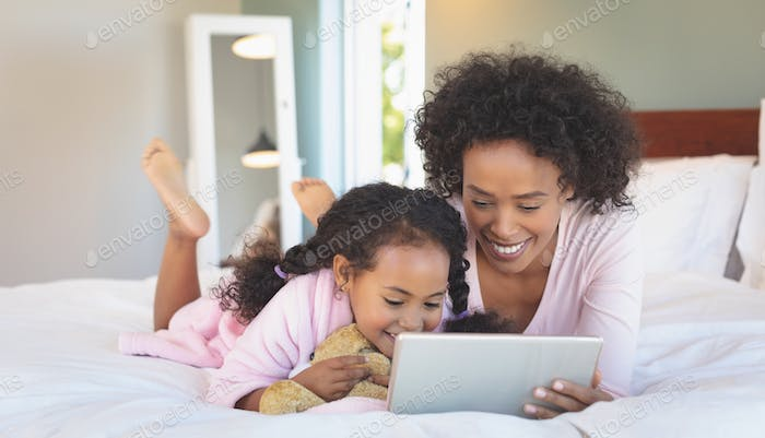 Happy African American mother and her cute daughter using digital tablet on bed in bedroom at home